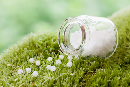 globules: Bottle of homeopathy globules on green moss. Selective focus. Stock Photo