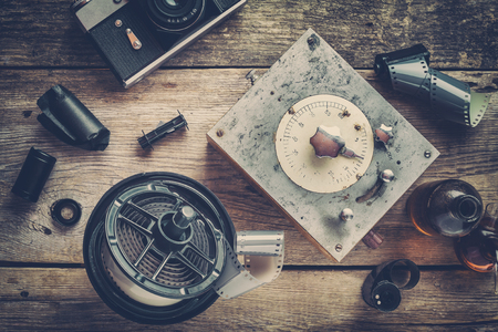 Developing tank with its film reels, photo film rolls, cassette, retro camera, timer, and chemical reagents. Stock Photo