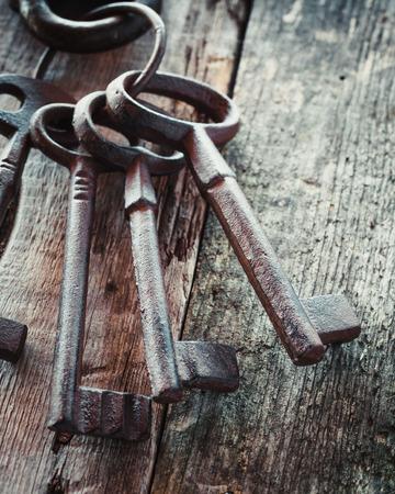 Old rusty keys on wooden background. Archivio Fotografico