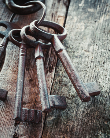 open door: Old rusty keys on wooden background. Stock Photo