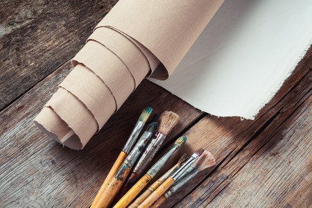 priming brush: Artist canvas in roll and paintbrushes on old rustic table
