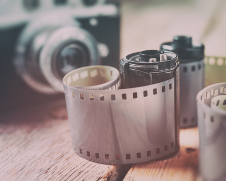 macro film: Old photo film rolls, cassette and retro camera on background. Vintage styled.