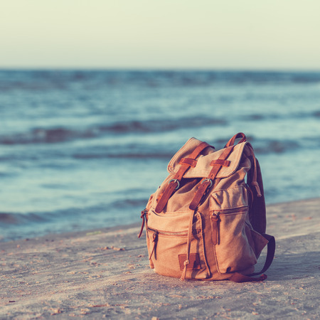 backpack: Travel Backpack on Summer Sea Beach. Stock Photo