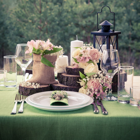 Wedding table setting decorated in rustic style. Retro styled photo Imagens