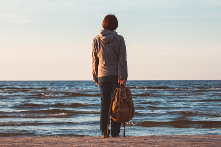 Young tourist woman with backpack  looking to sea at sunset. photo