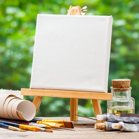 A blank canvas on easel, artistic paintbrushes, tubes of oil paint and bottle of flaxseed oil. Stockfoto