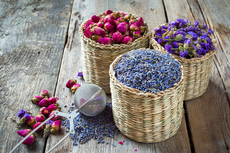 drink me: Herbal tea assortment: lavender, roses and chinese forget-me-not in wicker basket. Selective focus. Stock Photo