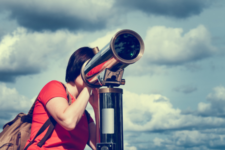Young woman looking through tourist telescope, exploring landscape. photo