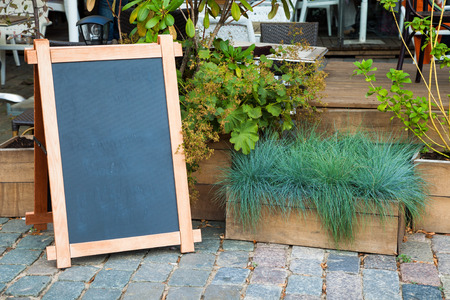 Empty menu advertising board and wooden box of grass near a restaurant Standard-Bild