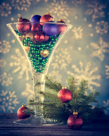 christmas decoration wine glass filled with christmas tree balls as festive cocktail retro styled
