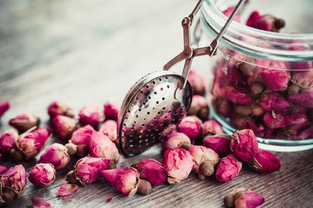 flores secas: Capullos de rosa de té, infusor de té y tarro de cristal. enfoque selectivo. Foto de archivo