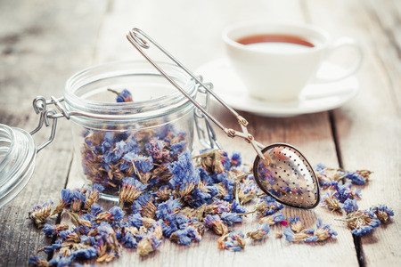 tea ceremony: Healthy forget me not tea in glass jar, strainer and tea cup on background. Selective focus. Stock Photo