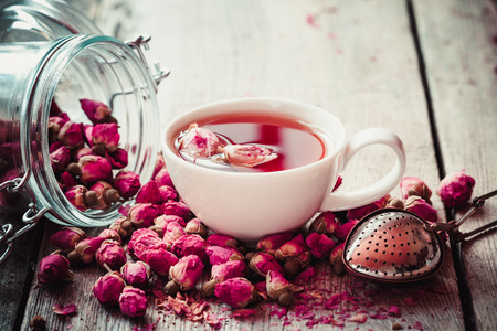 Rose buds tea, tea cup, strainer and glass jar with rosebuds. Selective focus.