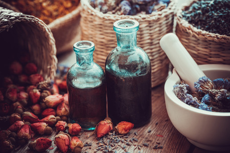 aromatherapy oil: Bottles of tincture, basket with rose buds, and dried forget me not flowers in mortar. Herbal medicine. Selective focus. Stock Photo