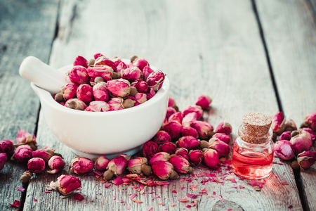 flores secas: Mortero con capullos de rosa y aceite de rosas esenciales. Enfoque selectivo.