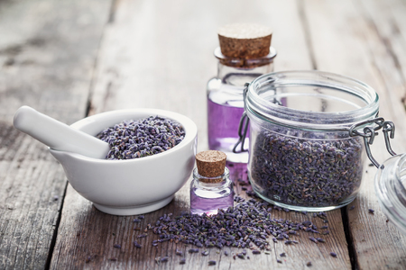 Dry lavender flowers in white mortar, glass jar of lavender and bottles of essential oil.  Selective focus