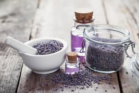 Trockene Lavendelblüten in Weiß Mörtel, Glas von Lavendel und Flaschen ätherisches Öl. Selektiver Fokus