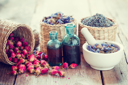 Bottles of tincture, basket with rose buds, lavender and dried forget me not flowers in mortar. Herbal medicine. Selective focus.