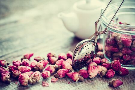 tea strainer: Rose buds tea, tea strainer closeup, glass jar and teapot on background. Selective focus.