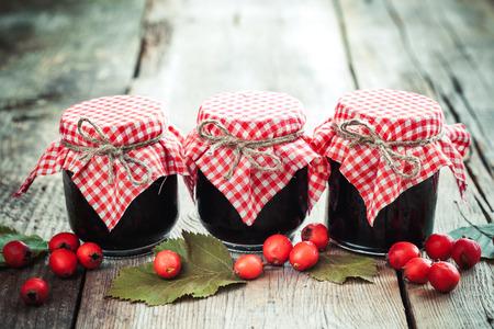 mermelada: Tres tarros de mermelada y bayas de espino en la mesa rústica
