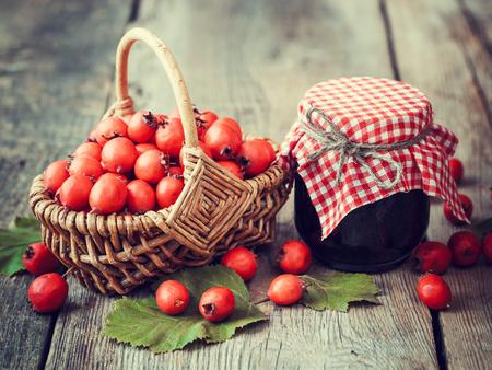 mermelada: Tarro de mermelada y bayas de espino en la cesta sobre la mesa rústica Foto de archivo