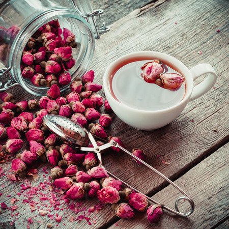 Dry rose flowers, tea cup, strainer and glass jar with rose buds. Selective focus. Retro styled photo. Foto de archivo