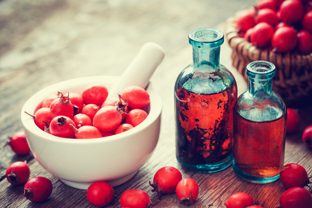 organic products: Mortar of hawthorn berries, two tincture bottles and thorn apples in basket on old wooden table. Herbal medicine. Selective focus. Stock Photo