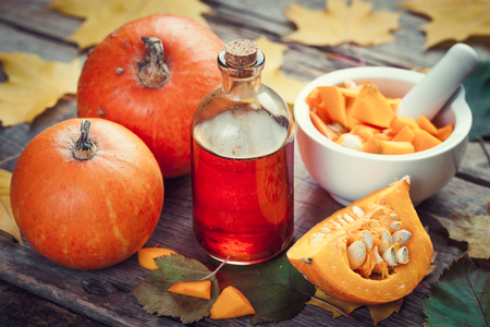 Pumpkin seeds oil bottle, pumpkins and mortar on wooden table with autumn leaves. Selective focus.