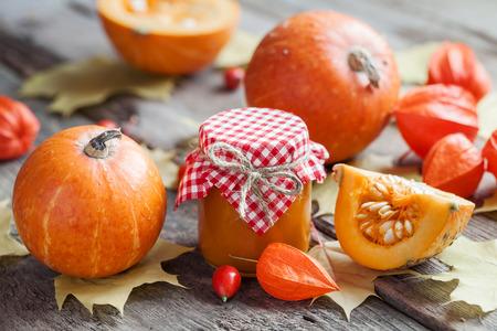 preserve: Pumpkin jam, puree or sauce and pumpkins on wooden table. Autumn still life. Selective focus.