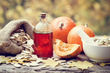 pumpkin seed: Pumpkin seeds oil bottle, pumpkins, canvas bag with seeds and mortar on wooden table. Selective focus.