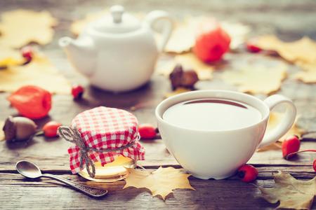 Tazza di tè, barattolo di miele e teiera su sfondo. Autunno still life. Messa a fuoco selettiva.