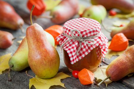 mermelada: Mermelada de peras y peras maduras en la vieja mesa de madera. Todavía del otoño vida. Enfoque selectivo.
