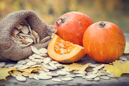pumpkin leaves: Pumpkins and canvas bag with pumpkins seeds on wooden table. Selective focus. Stock Photo