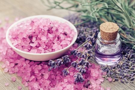 bath essence: Aromatic sea salt, bottle of essential oil and lavender flowers. Selective focus. Stock Photo