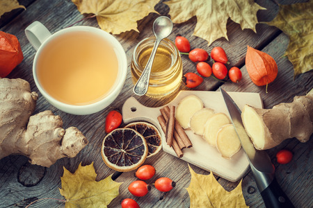 Healthy ginger tea, jar of honey, ginger root, dried lemon slice, wild briar and cinnamon on table with autumn maple leaves. Top view. Imagens - 47628006