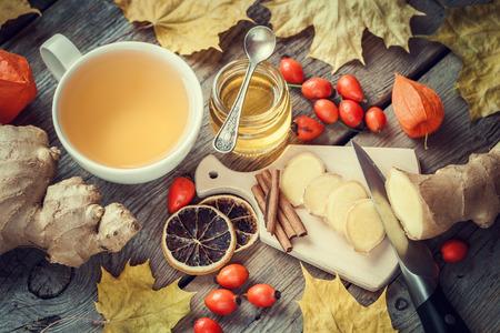 jengibre: Saludable té de jengibre, tarro de miel, raíz de jengibre, rodaja de limón seca, brezo salvaje y la canela en la mesa con hojas de arce. Vista superior.