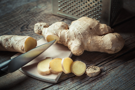ginger health: Ginger on cutting board and grater on kitchen table. Selective focus.