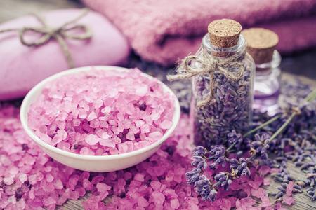 Aromatische zeezout, fles van droge lavendel, etherische olie en lavendel bloemen. Bar van zelfgemaakte zeep en handdoek op de achtergrond. Selectieve aandacht.