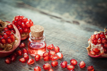 cosmetic product: Pomegranate oil in bottle and garnet fruit with seeds on table. Selective focus.