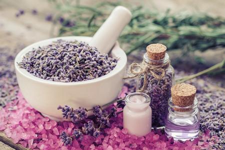 lavender flowers: Dry lavender in mortar, aromatic pink sea salt, cream, bottles of essential oil and lavender flowers. Selective focus.