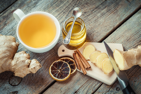 illness: Ginger on cutting board, jar of honey, tea cup on kitchen table. Top view. Stock Photo