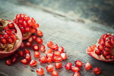 Pomegranate slices and garnet fruit seeds on table. Selective focus.