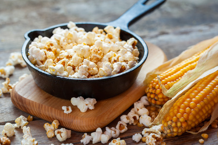 Prepared popcorn in frying pan on cutting board, corn seeds in bowl and corncobs on kitchen table. Selective focus. Stock Photo