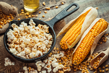 popcorn bowls: Prepared popcorn in frying pan, corn seeds in bowl and corncobs on kitchen table. Selective focus. Stock Photo