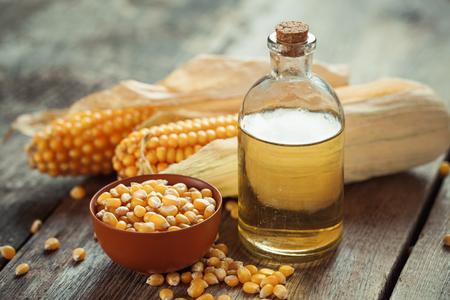 Corn etherische olie fles, zaden in kom en maïskolven op de keukentafel. selectieve aandacht
