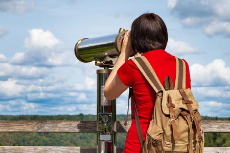 Young woman looking through tourist telescope, exploring mountain landscape. photo