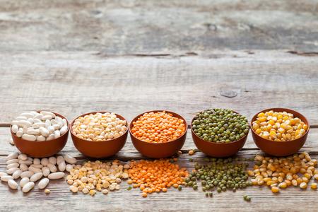 garbanzos: Cuencos de granos de cereales: lentejas rojas, mungo verde, maíz, frijoles y guisantes en la mesa de madera.
