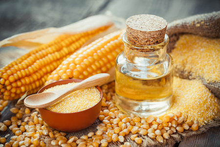 corn flour: Corn essential oil bottle, corn groats, dry seeds and corncobs on wooden rustic table. Selective focus
