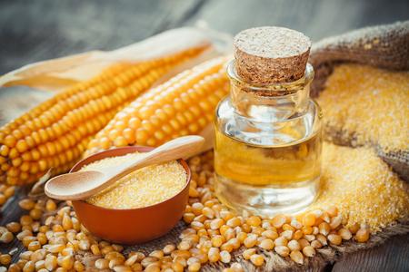 elote: Maíz botella de aceite esencial, grañones de maíz, semillas secas y mazorcas de maíz en la mesa de madera rústica. Enfoque selectivo
