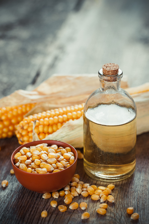 mais: Corn essential oil bottle, seeds in bowl and two corncobs on kitchen table. Selective focus